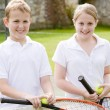 Two young friends with rackets on tennis court smiling — Stock Photo