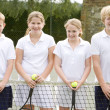 Four young friends with rackets on tennis court smiling — Stock Photo #4780034