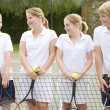 Four young friends with rackets on tennis court smiling - Stok fotoğraf