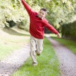Young boy running on a path outdoors smiling — Stock Photo #4780038