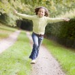 Young girl running on a path outdoors smiling — Stock Photo