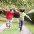 Two young friends running on a path outdoors — Stock Photo