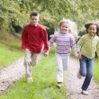 Three young friends running on a path outdoors smiling — Stock Photo #4780041