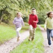 Three young friends running on a path outdoors smiling — Foto de Stock