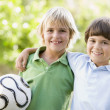 Two young boys outdoors with soccer ball smiling — Stock Photo #4780047