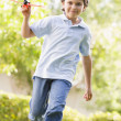 Young boy with toy airplane running outdoors smiling — Stock Photo