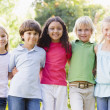 Five young friends standing outdoors smiling — Stock Photo #4780052