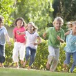 Five young friends running outdoors smiling — Zdjęcie stockowe #4780053