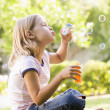 Young girl blowing bubbles outdoors — Stock Photo
