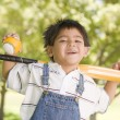 Young boy holding baseball bat outdoors smiling — Stock Photo