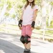 Young girl outdoors on inline skates smiling — Stock Photo