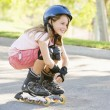 Stock Photo: Young girl outdoors on inline skates smiling