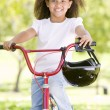 Young girl on bicycle outdoors smiling - 