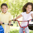 Brother and sister outdoors with scooter and bicycle smiling — Stock Photo