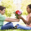 Young boy giving young girl flowers and smiling — Stock Photo