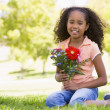 Royalty-Free Stock Photo: Young girl holding flowers and smiling