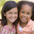 Stock Photo: Two young girl friends sitting outdoors smiling