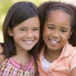 Two young girl friends sitting outdoors smiling — Stock Photo