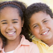 Brother and sister outdoors smiling — Stock Photo
