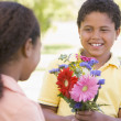 Young boy giving young girl flowers and smiling — Stock Photo #4780137