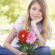 Stock Photo: Young girl holding flowers and smiling