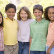 Five young friends standing outdoors smiling — Stock Photo #4780159