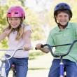 Brother and sister outdoors on bicycles smiling — Stock Photo