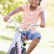 Young girl on bicycle outdoors smiling — Stock Photo