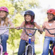 Three young girl friends outdoors on bicycles smiling — Stock Photo #4780177