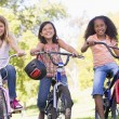 Three young girl friends outdoors on bicycles smiling — Stock Photo