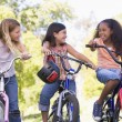 Three young girl friends outdoors on bicycles smiling — Foto Stock