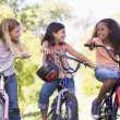 Three young girl friends outdoors on bicycles smiling — Stockfoto #4780182