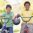 Two young boys on bicycles outdoors smiling - Stock Photo