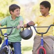 Two young boys on bicycles outdoors smiling — Stock Photo