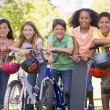 Five young friends with bicycles scooters and skateboard outdoor — Stock Photo
