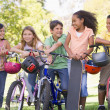 Five young friends with bicycles scooters and skateboard outdoor - Stock Photo