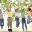 Five young friends jumping outdoors smiling — Stock Photo #4780190