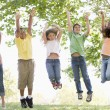 Five young friends jumping outdoors smiling - Foto Stock