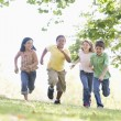 Five young friends running outdoors smiling — Stock Photo #4780192