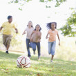 Five young friends playing soccer — Stock fotografie