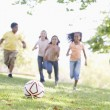 Five young friends playing soccer — ストック写真
