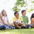 Five young friends sitting outdoors with soccer ball looking up — Stockfoto