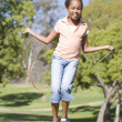 Young girl using skipping rope outdoors smiling — Stock Photo