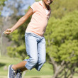 Stock Photo: Young girl using skipping rope outdoors smiling