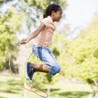 Young girl using skipping rope outdoors smiling — Stock Photo #4780204