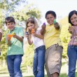 Five young friends with water guns outdoors smiling — Stock Photo #4780206