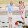 Brother and sister at beach with nets and pail — Stock Photo
