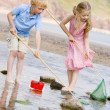 Brother and sister at beach with nets and pail — Stock Photo #4780213