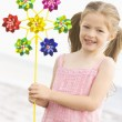 Young girl at beach with toy windmill smiling - Stock Photo