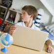 Young Boy Using A Laptop In His Bedroom — Stock Photo
